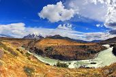 Travel to Chile. The river bends a horseshoe under the flying clouds. The picture was taken Fisheye