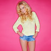 Glamorous blond woman with her long hair in ringlets in trendy skimpy denim shorts posing confidentl
