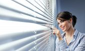 Attractive Woman Peeking Through Blinds