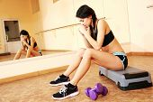 Young tired fit woman resting at gym