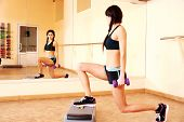 Young happy fit woman doing exercises with dumbells on step board and looking on her reflection in mirror at gym