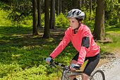 Woman mountain biking in forest on sunny day cycling path