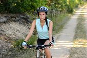Woman mountain biking on countryside path recreation