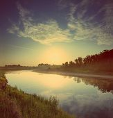 beautiful morning landscape with sunrise over river - vintage retro style