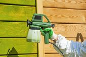stock photo of air paint gun  - Hand painting wooden wall with spray gun in green - JPG