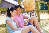 Asian Couple Resting By Fence With Old Fashioned Cycle