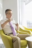 Mature businessman having coffee in lobby at office