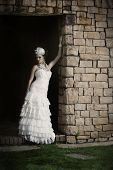 Beautiful bride in vintage dress leaning against brick wall