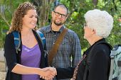 image of professor  - Female university students shaking hands at university campus with professor - JPG