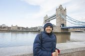 Portrait of mid adult man in warm clothing standing in front of tower bridge; London; UK