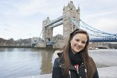 Portrait of beautiful young woman standing in front of tower bridge; London; UK