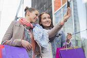 foto of two women taking cell phone  - Female friends with shopping bags taking self portrait through mobile phone - JPG
