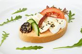 Sandwich with cheese and vegetables on white dish
