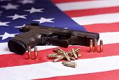 foto of ammo  - A conceptual image of a pistol and ammo on a US flag - JPG