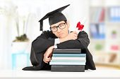 Worried college graduate leaning on a stack of books, indoors