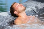 Wellness Spa - man relaxing in hot tub whirlpool Jacuzzi outdoor at luxury resort spa retreat. Handsome young male model relaxed with eyes closed resting in water near pool on travel vacation holiday.