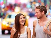 People in New York - happy couple on Times Square. Dating young couple in love walking and talking.