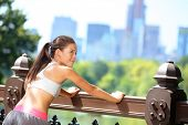 Running woman stretching after jogging in New York City, Central Park, Manhattan. Fit runner fitness