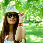 fashion girl outdoor portrait, young woman walking in summer park  in sunglasses and fedora with long brown hair