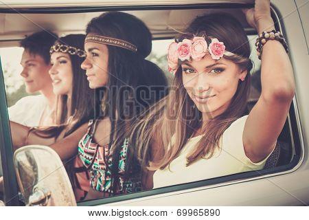 Multi-ethnic hippie friends in a minivan on a road trip poster