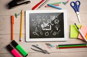 Composite image of digital tablet on students desk showing education doodles