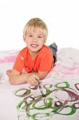Happy little boy painting on the floor on white background