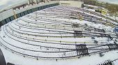 Depot with many railway lines covered with snow at autumn day, aerial view