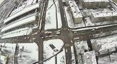 Urban landscape with snow-covered streets with wide road on a cloudy day, aerial view