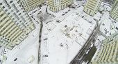 Snow-covered courtyard of modern residential complex, aerial view