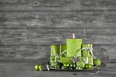 Wooden Christmas Or Advent Background With Green Decoration, Candle And Presents.