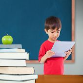 Cute boy using tablet against green apple on pile of books in classroom