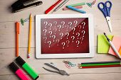 picture of punctuation marks  - Composite image of digital tablet on students desk showing question marks - JPG