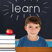 The word learn and cute boy smiling against red apple on pile of books in classroom