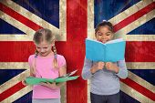 Elementary pupils reading against union jack flag in grunge effect