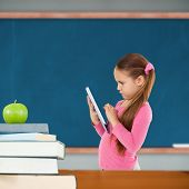 Cute girl using tablet against green apple on pile of books in classroom