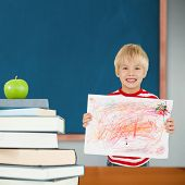 Cute boy showing his art against green apple on pile of books in classroom