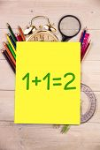 One plus one equals two against students desk with yellow page
