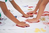 Cute little boys painting on floor in classroom at the nursery school