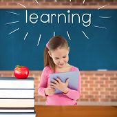 The word learning and cute girl using tablet against red apple on pile of books in classroom