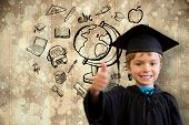 Cute pupil in graduation robe against paint splattered paper