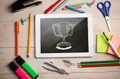 Composite image of digital tablet on students desk showing winners cup doodle