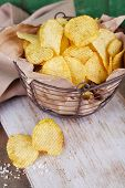 Tasty potato chips in metal basket on wooden table