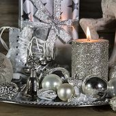 Festive Christmas Decoration In Silver With Burning Candles.