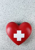 Red heart with cross sign on color background