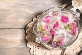Ice cubes with rose flowers in glass bucket and two glasses with champagne on wooden table backgroun