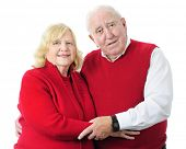 A senior couple happily standing together in their red sweaters.  On a white background.