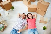 Happy young couple looking at camera while lying on the floor of new house