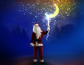 Santa Claus holding moon in night sky on rope