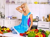 Unhappy tired woman preparing food at kitchen.