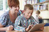 School Pupil With Teacher Using Digital Tablet In Classroom